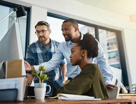 Três pessoas a trabalhar em equipa no computador