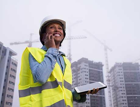 mulher a trabalhar em construção civil ao telemóvel