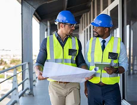Dois homens a conversar sobre projeto de construção civil