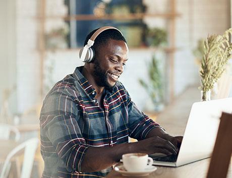 homem angolano com airpods a trabalhar no computador