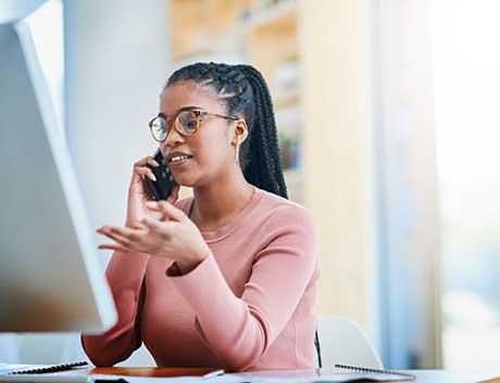 mulher angolana a conversar ao telemóvel enquanto trabalha