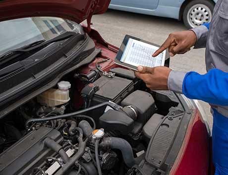 mecânico a trabalhar no motor do carro enquanto usa o tablet