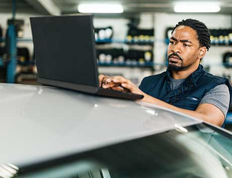 homem angolano a trabalhar no computador na oficina